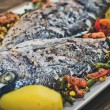 Closeup of grilled dorada garnished with potato and vegetables — Stock Photo #76594571