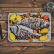 Grilled dorada garnished with potato and vegetables — Stock Photo #76594577