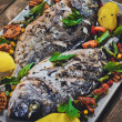 Closeup of grilled dorada garnished with potato and vegetables — Stock Photo #76594581