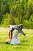 Couple doing yoga exercises in the wood — Stock Photo