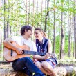 Portrait of young loving happy couple with guitar in forest — Stock Photo #76138023