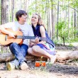 Portrait of young loving happy couple with guitar in forest — Stock Photo #76138029
