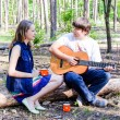 Portrait of young loving happy couple with guitar in forest — Stock Photo #76138049