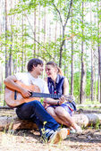 Portrait of young loving happy couple with guitar in forest — Stockfoto