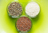 Flax, sesame, and cannabis seeds in glass bowls — Stock Photo