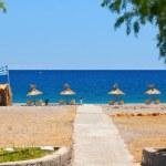 Pebble beach with wooden umbrellas. Rhodes Island, Greece. — Stock Photo #75151767