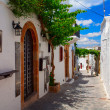Narrow street with old white houses. Lindos town. Rhodes, Greece. — Stock Photo #75151847
