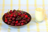 Red sweet cherries with water drops and glass of milk — Stock Photo