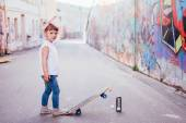 Young skater by the graffiti wall — Stockfoto