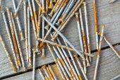 Paslı çivi ahşap tahta üzerinde dağınık — Stok fotoğraf