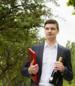 Young man with champagne and chocolates — Stock Photo