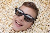 Laughing young boy in stereo glasses looking out of popcorn — Stock Photo