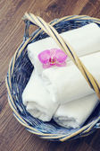 Fleur d'orchidée avec des serviettes dans un panier d'osier sur un fond en bois — Photo