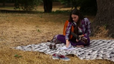 Girl composes music with a guitar. — Stock Video