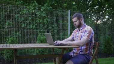 Man writing on a laptop, sitting on wood chair in small garden. — Stock Video