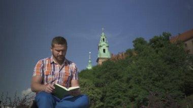 Uomo smette di leggere il libro e guardare rotondo. — Video Stock