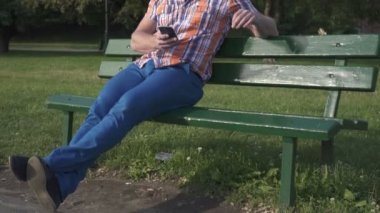 Man browsing smartphone, sitting on wood brench, tilt and pan shot — Stock Video