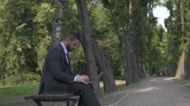 Businessman working on laptop, sitting on bench in park, pan and tilt shot. — Stock Video