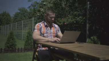 Man sitting in the garden and typing on the laptop. — ストックビデオ