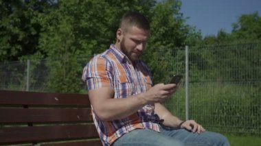 Man is sitting on wooden bench and browsing smartphone. — Stock Video