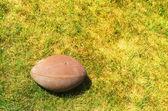 美式足球在黄色绿色草地上的球 — 图库照片