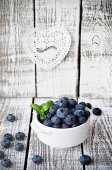 White bowl  with blueberries on the white wooden table with basil leaf — Stock Photo