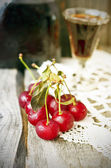 Cherry liquor in the little glasses and big bottle on the vintage napkin on the old wooden background — Stock Photo
