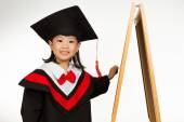 Asian Chinese little girl in graduation gown againts blackboard — Stock Photo