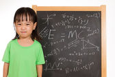 Asian Chinese little girl againts blackboard with formulas — Stock Photo