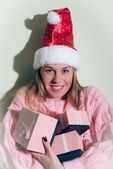Santa Girl in Christmas hat with gifts boxes — Stock Photo