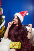 Portrait of pretty girl having fun in santa hat holding gift box & eating slice of orange sitting on blue light copy space — Stock fotografie