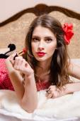 Closeup portrait of making red lipstick & looking at camera thoughtfully beautiful pinup girl having fun relaxing in bed on light copy space background — Stock Photo