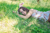 Young woman lying on soft  fresh spring grass daydreaming — Stock Photo