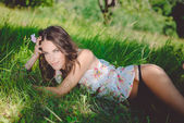 Beautiful brunette girl wearing top and black strings lying on grass — Stock Photo