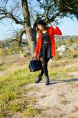 Charming girl wearing red coat with black handbag in countryside — Stock Photo