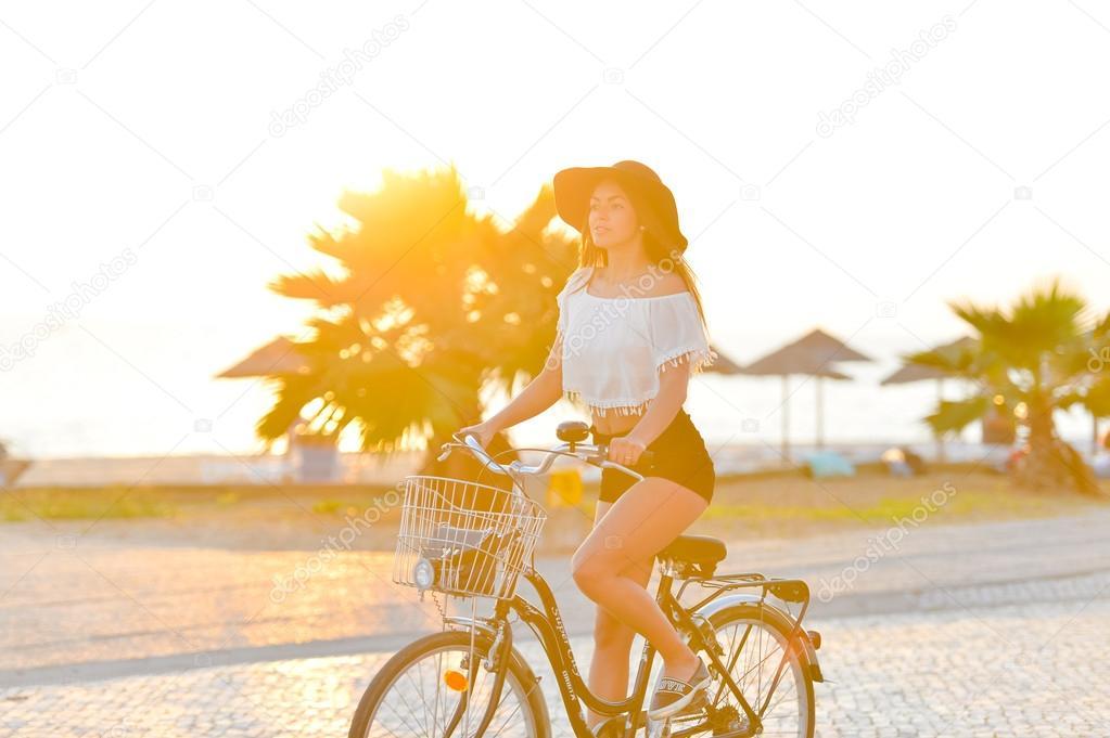 Девушка в шляпе на велосипеде фото