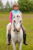 Young girl child sitting astride a white horse and smiling  Outdoors — Stock Photo