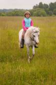 Small child riding on a white horse and smiling  Outdoors — Stock Photo