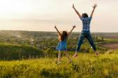 Mother and daughter leap at sunset — Stock Photo