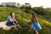 Mother and daughter blowing soap bubbles — Stock Photo