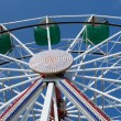 Middle and upper part of ferris wheel with green bowls against blue sky with thin clouds. There are some passengers visible. Red, Blue and White lightbulbs are on the supporting structure — Stock Photo #74462921