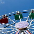 Middle and upper part of ferris wheel with red and green bowls against blue sky with thin clouds. Blue and White lightbulbs are on the supporting structure — Stock Photo #74463645