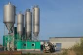 Burgum, Sumar, Niederlande, 27. April 2015. Noppert Beton-Fabrik. Eine konkrete Produktionsstätte. des Silos Leuchten im Sonnenuntergang schön. Ein Zement-Lkw wartet neben der Baracke. Eine weitere versteckt sich im Schatten. — Stockfoto