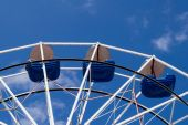 Upper part of ferris wheel with blue bowls against blue sky with thin clouds — Stock Photo