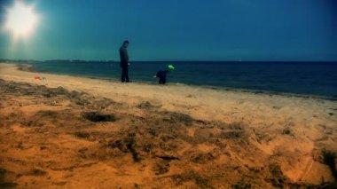 Pappa och lilla pojke spelar på stranden — Stockvideo