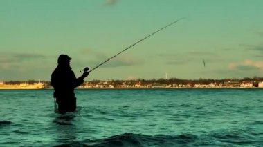 Fisherman in water at sunset panning — Stock Video
