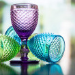Multi color little glasses with reflection in bokeh background — Stock Photo #74537009
