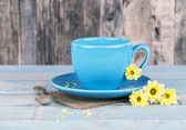 Blue coffee cup with yellow flowers — Stock Photo