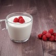 Raspberry on a table and in glass of yogurt — Stock Photo #77804140