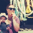 Little baby girl sitting with her mother on the beach eating aan ice-cream with her hat on — Stock Photo #74356529